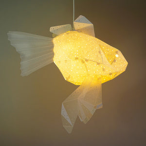 Origami-styled lamp in the form of goldfish, yellow color, the light is on, dark background.