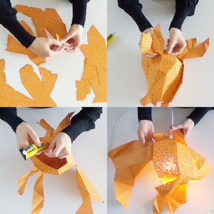 Woman's hands fold and glue the orange Fish lantern from the pre-cut templates.
