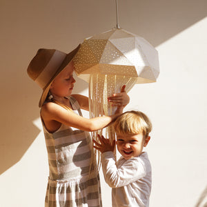 Two kids, a girl and a boy, hold lamp in the form of jellyfish in their hands.