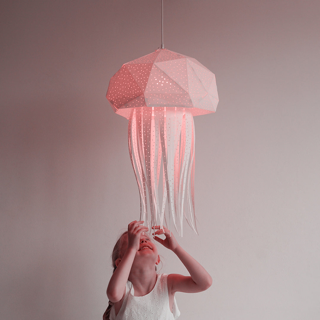 Little girl reaches out for big lamp in the form of jellyfish.