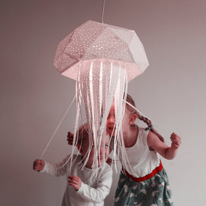 Two kids, a girl and a boy, play with a big lamp in the form of jellyfish.