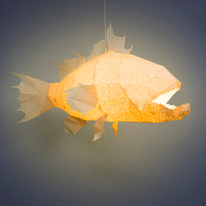 Lighted white lamp in the form of marine fish with sharp teeth on dark background.