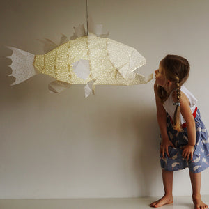 Girl plays with lighted white lamp in the form of marine fish with sharp teeth.