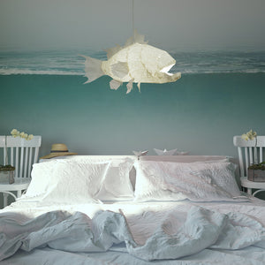 White lamp in the form of marine fish with sharp teeth hangs above the bed in a hotel.