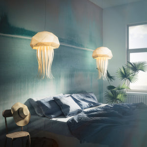 Two lighted lampshades in the form of jellyfish hang above the hotel's bed, morning light.