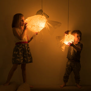Dark kid's room where the children, girl and boy, hold geometric lighted lamps which have form of Mommy  and Baby Goldfish.