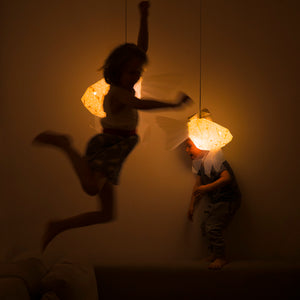 Dark kid's room where the children, girl and boy, play with geometric lighted lamps which have form of Mommy  and Baby Goldfish.