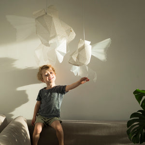 Kid's room where boy plays with geometric lighted lamps which have form of Mommy  and Baby Goldfish.