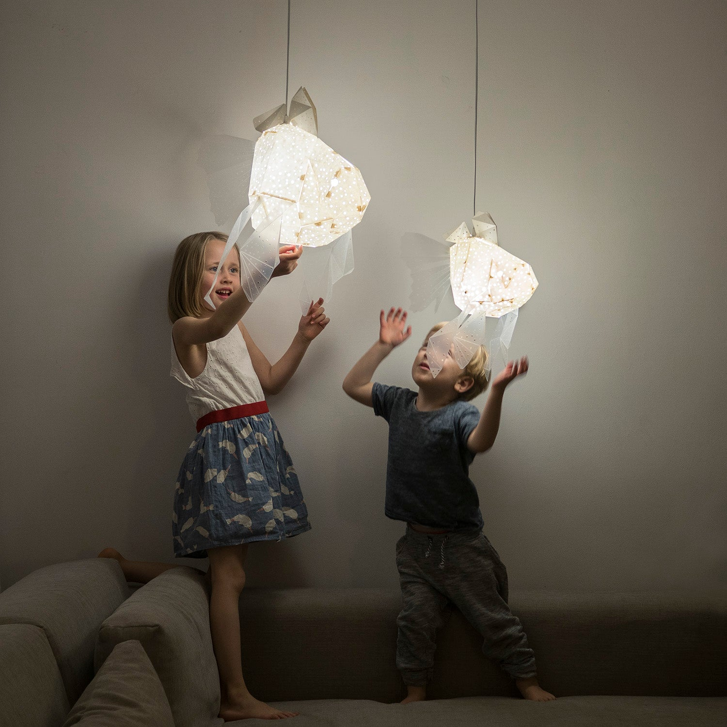 Kid's room where the children, girl and boy, play with geometric lighted lamps which have form of Mommy  and Baby Goldfish.