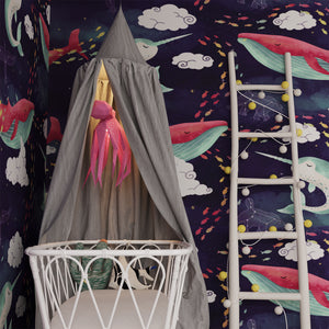 There is a pink paper lantern in the form of Octopus in kids' room with sea-inspired wallpaper, hanging above the bed with the grey baby's canopy.