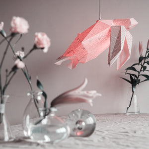 Pink lamp in the form of Sea Turtle hangs above the table, there are ases with flowers on the table.