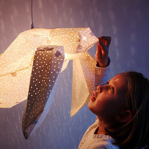 Girl plays with big white lamp in the form of Sea Tutle, the light is on.