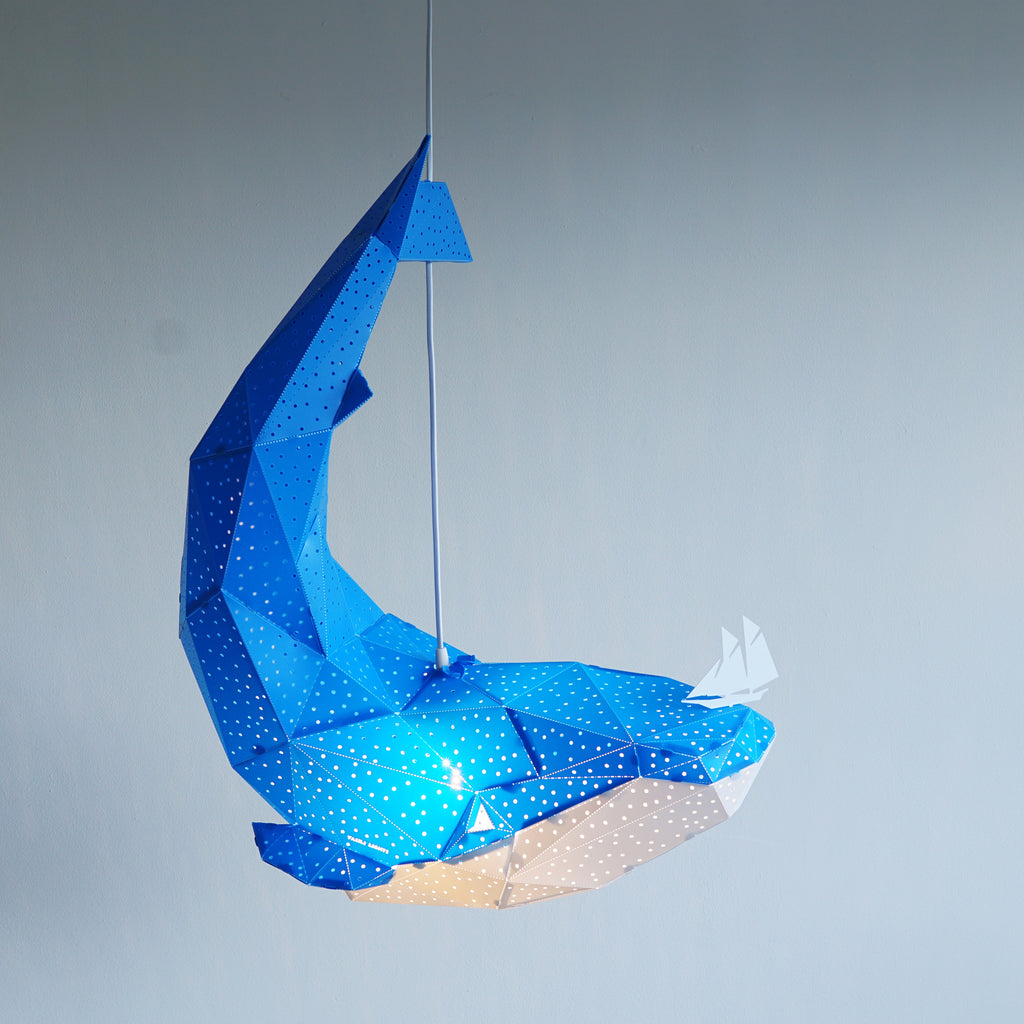 Side view of blue pendant lamp in the form of a whale that holds a little boat on his nose.
