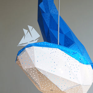 Close-up of blue pendant lamp in the form of a whale that holds a little boat on his nose.