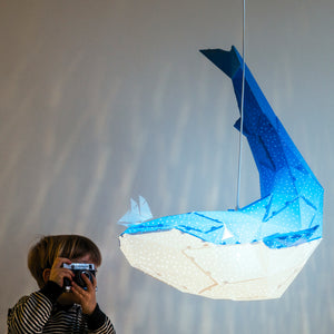 Boy takes picture of blue pendant lamp in the form of a whale that holds a little boat on his nose.