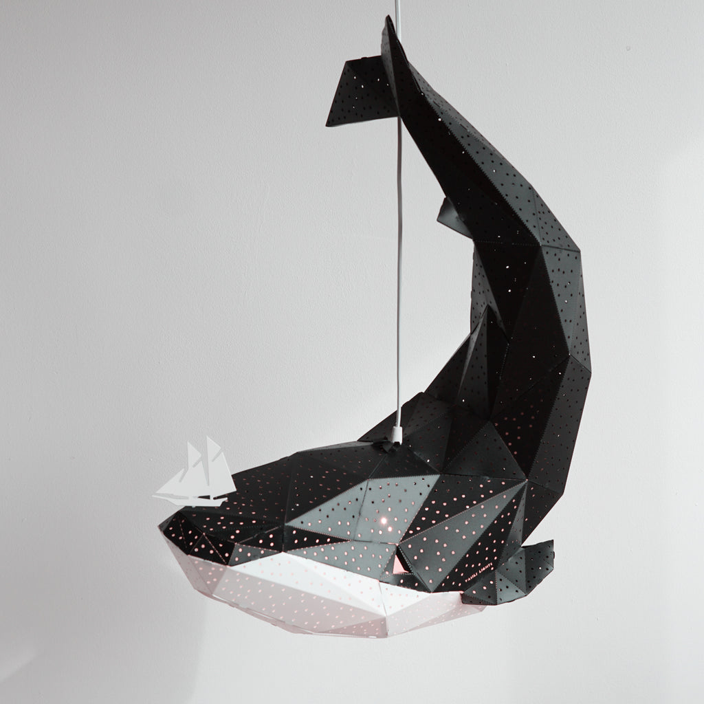 Side view of black pendant lamp in the form of a whale that holds a little boat on his nose.
