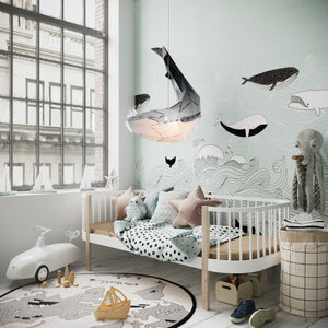 Black pendant lamp in the form of a whale that hangs in the sea-themed kids'room.