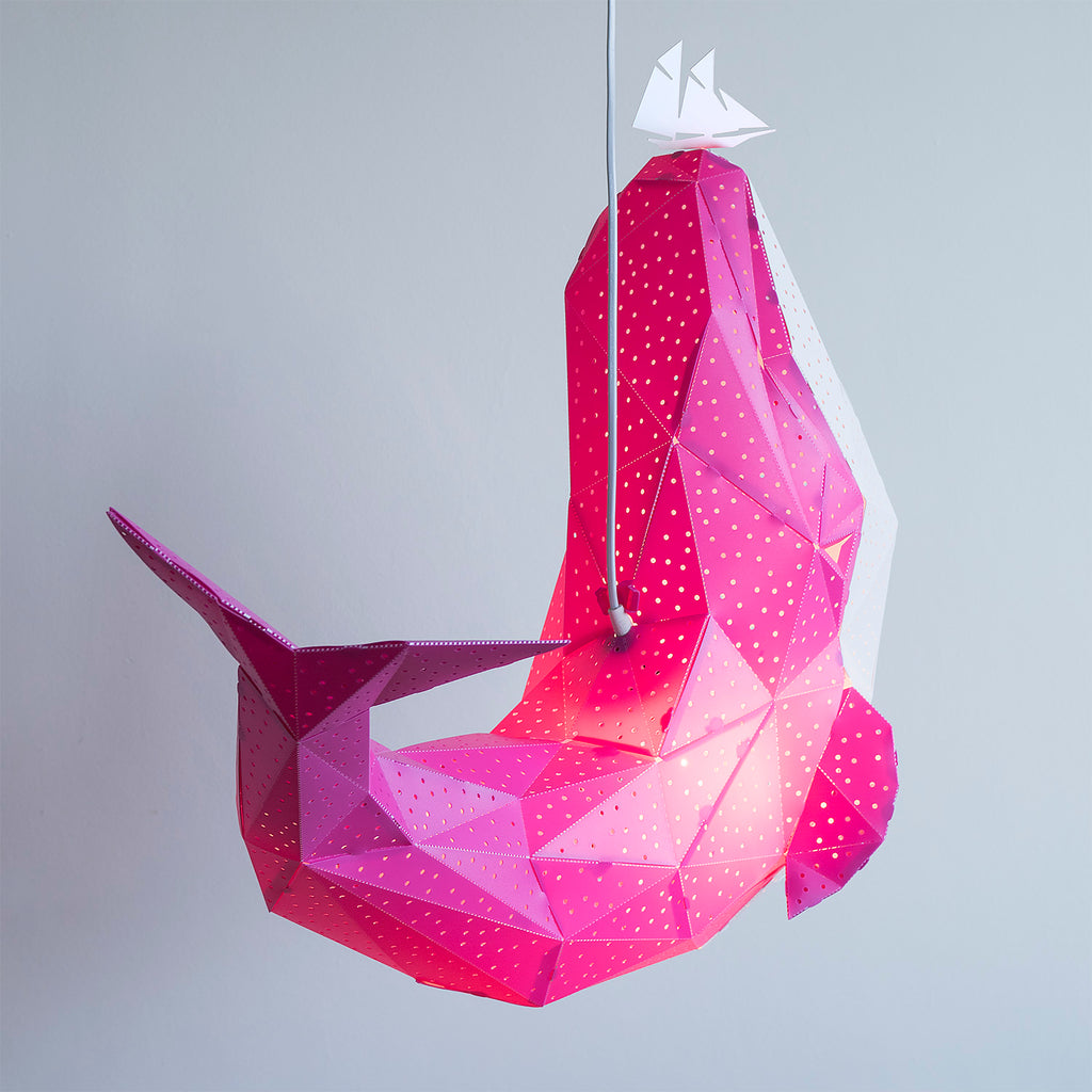 Back view of the pink pendant lamp in the form of a whale that holds a little boat on his nose.