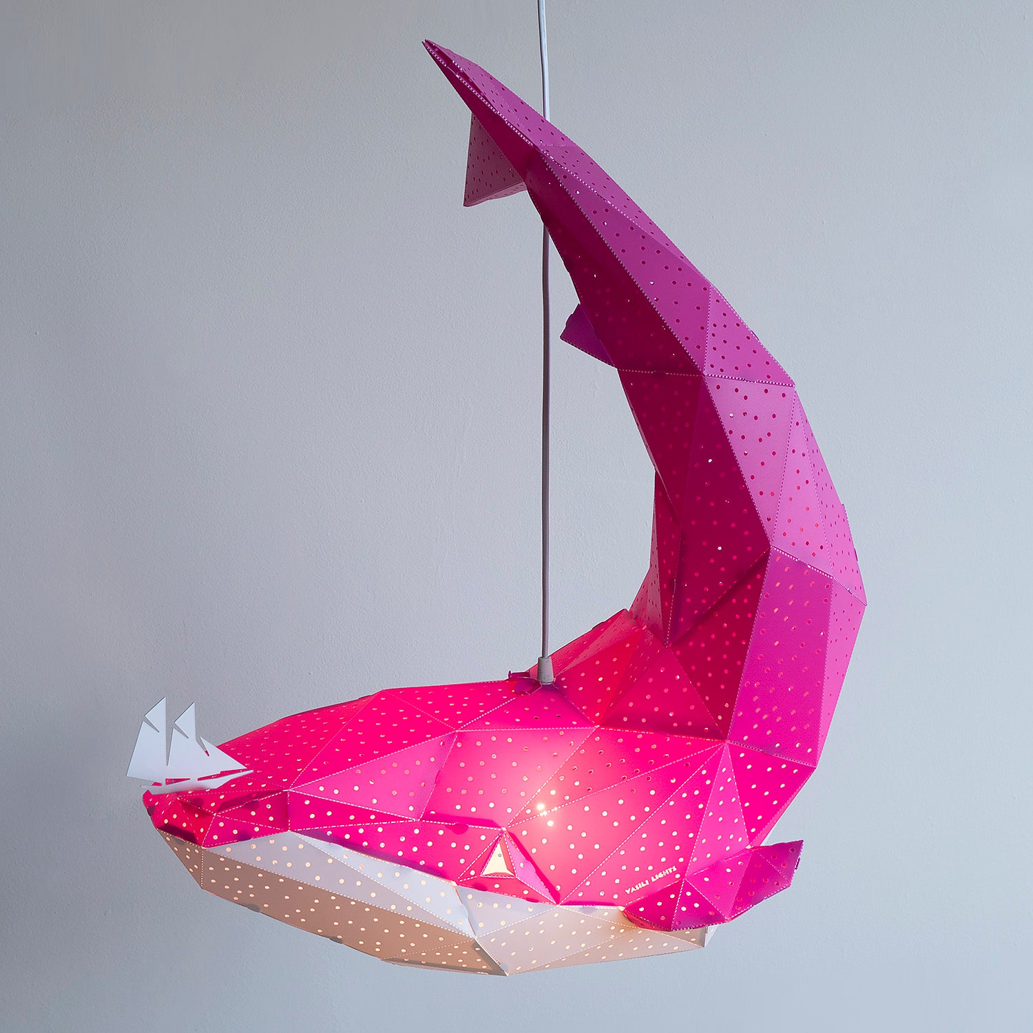 Side view of the pink pendant lamp in the form of a whale that holds a little boat on his nose.