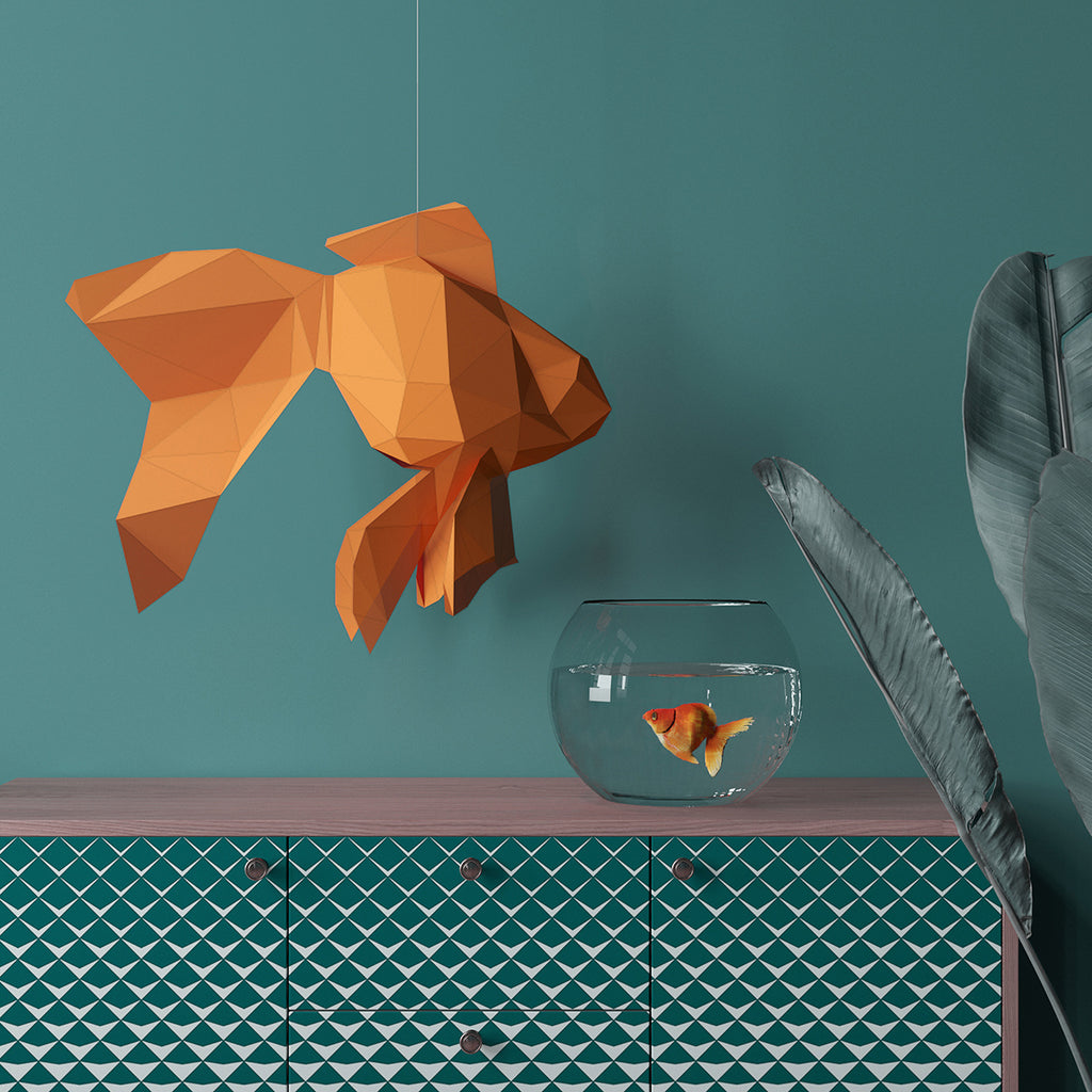 Goldfish paper sculpture hangs near the aquarium with a goldfish.