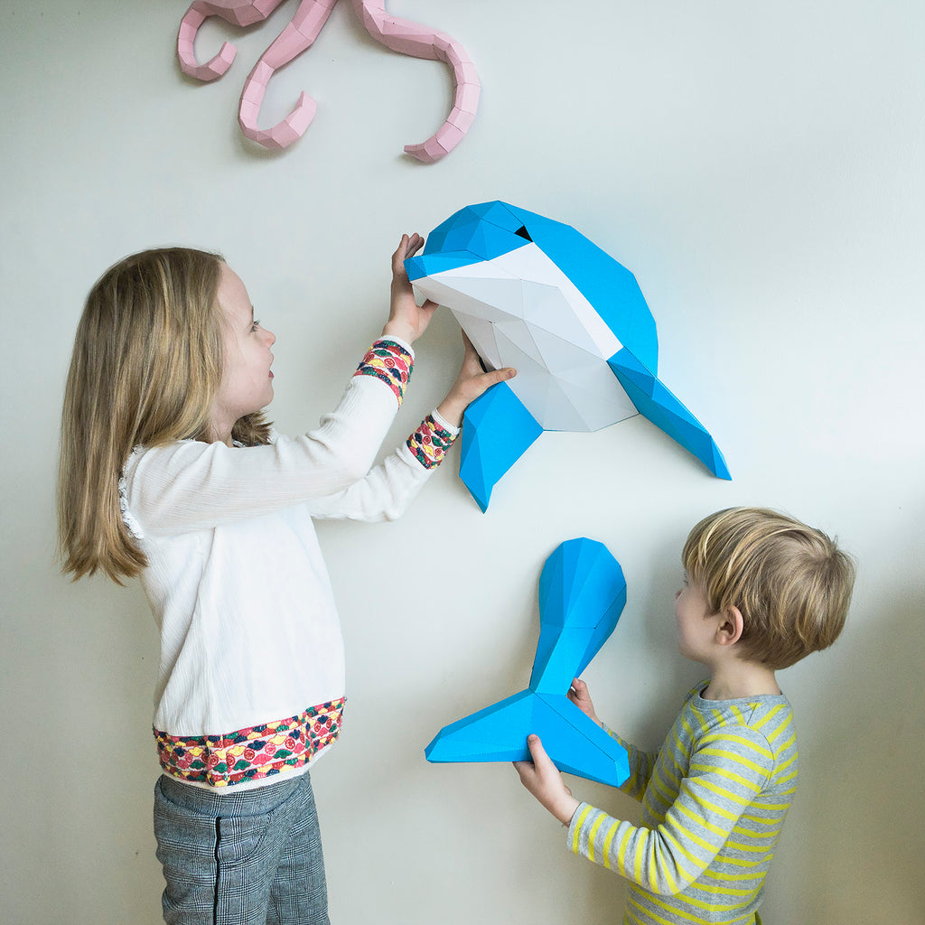 Girl and boy looking at paper sculpture of Dolphin on the wall.