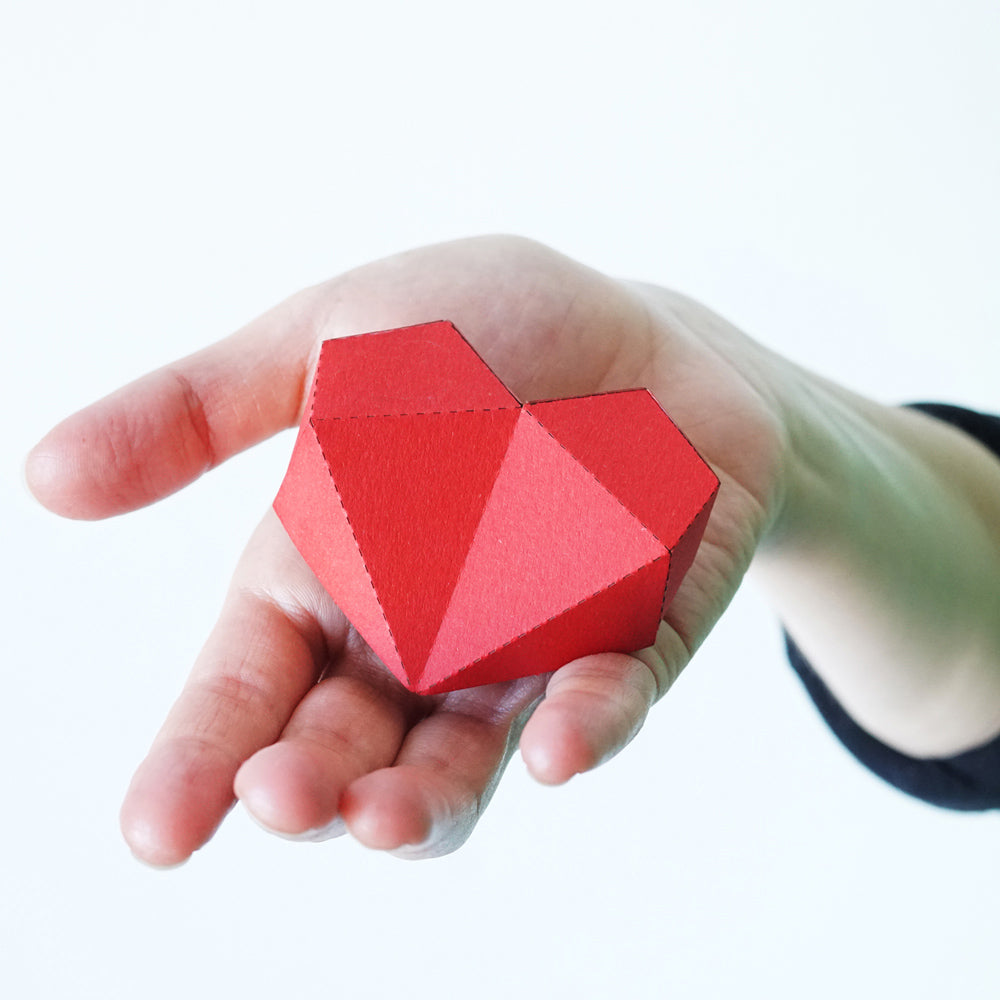 Hand holds 3D red heart paper sculpture.
