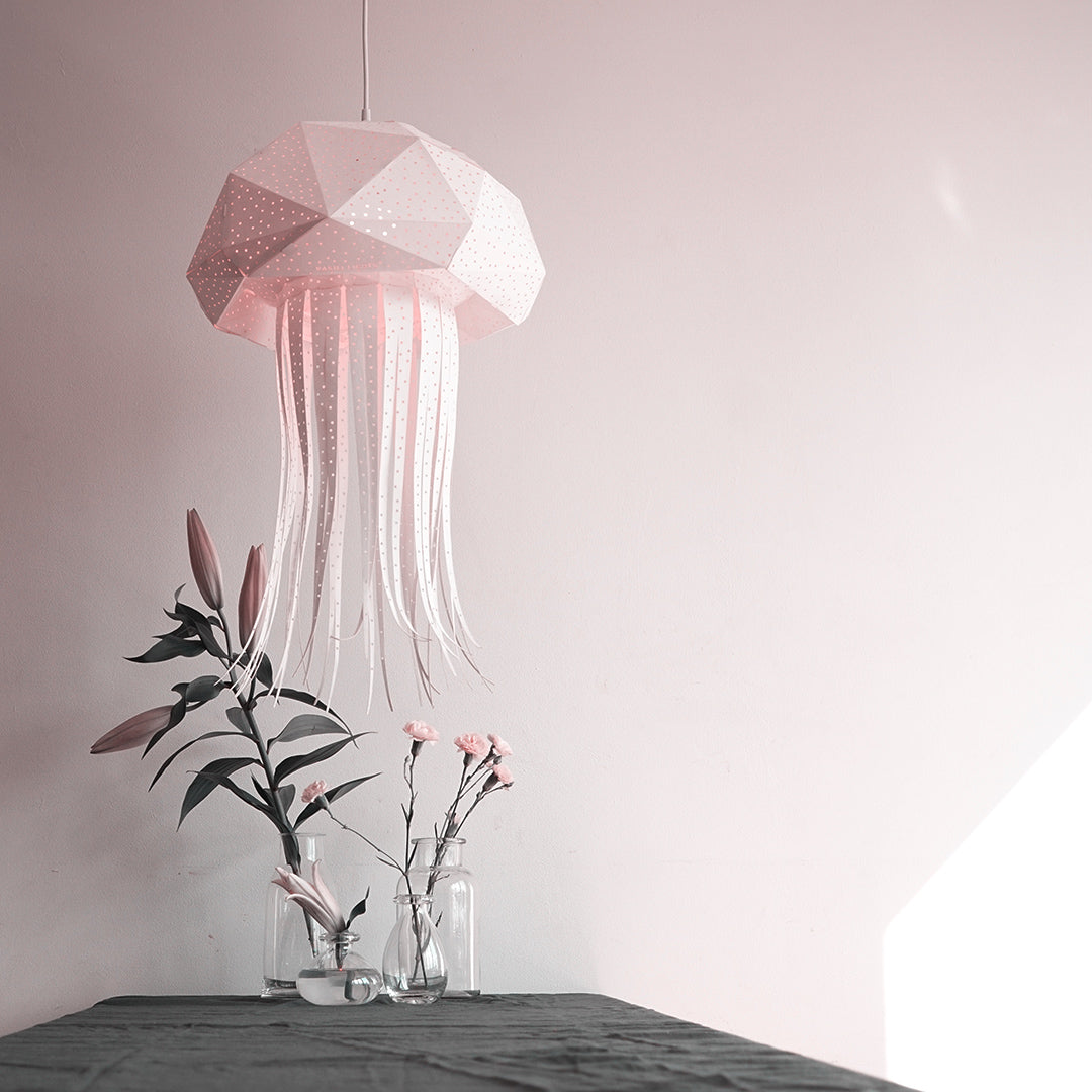 White lamp in the form of jellyfish hangs above the table, a vase with a flower is on the table.