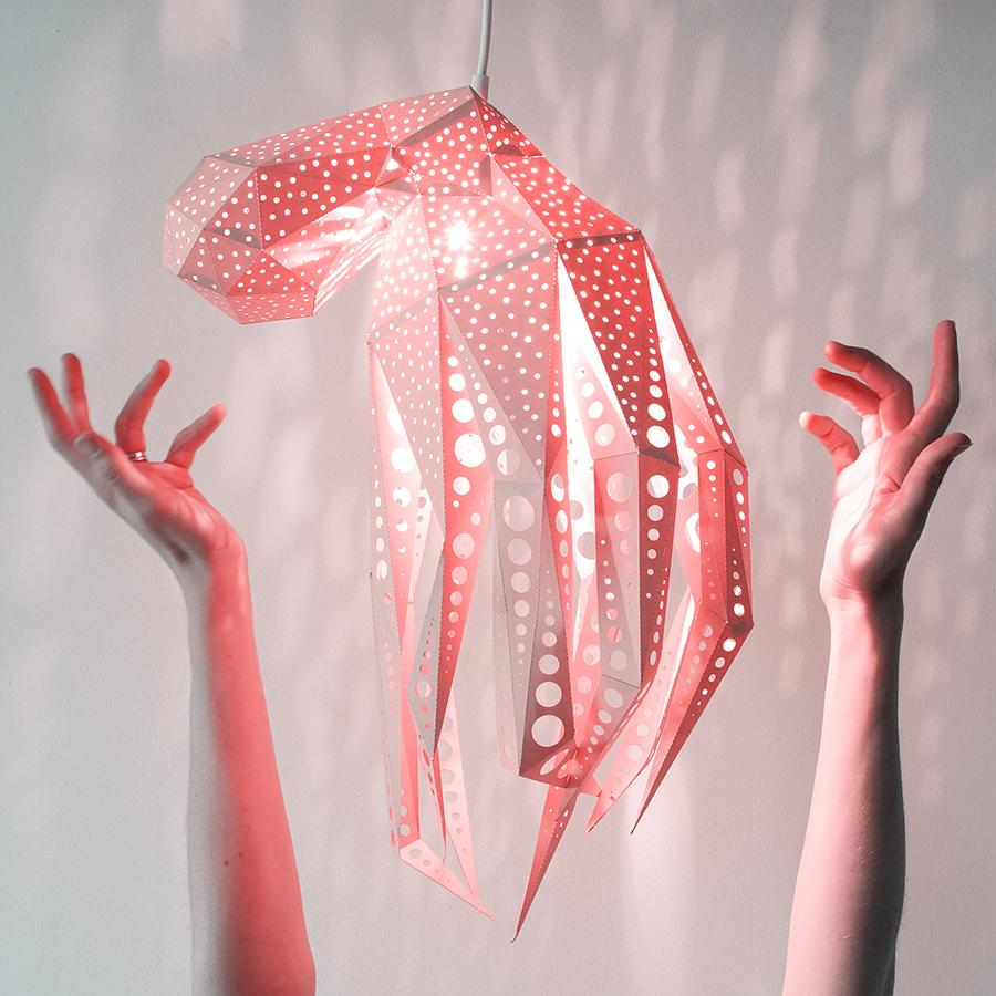 Woman's hands reach out for the pink Octopus lantern, hanging on a white background.