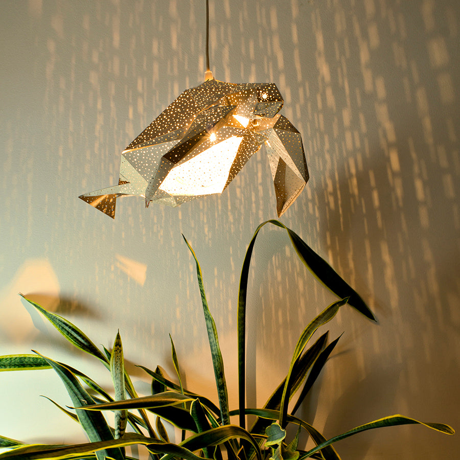 There is DIY grey paper Sea Turtle lantern hanging above a plant.