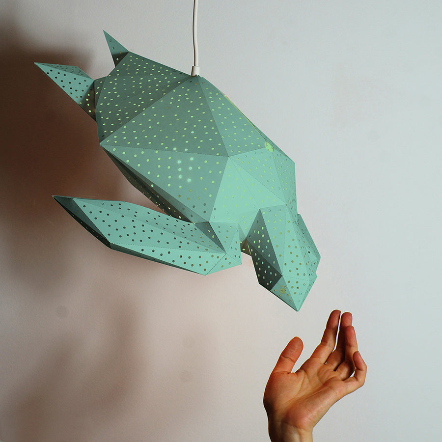 Woman's hand reaches out for the green Sea Turtle lantern, hanging on the white background.