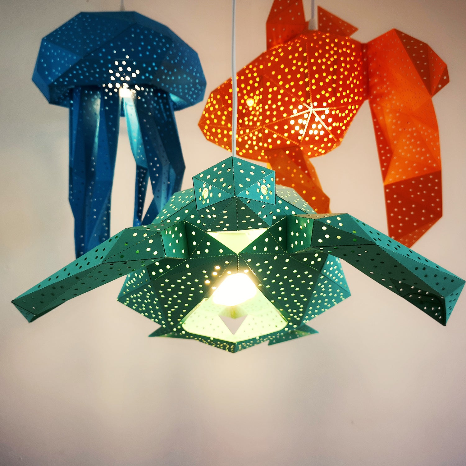 There is the green Sea Turtle lantern and orange Fish and blue Jellyfish hanging behind.
