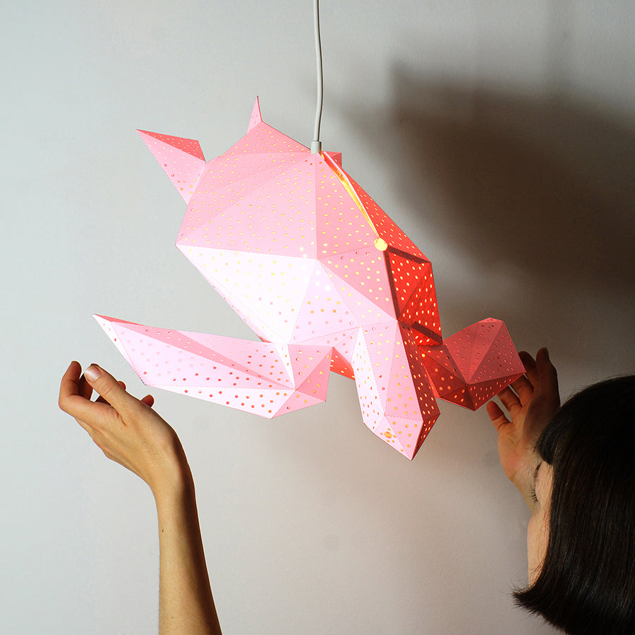 Woman's hand reaches out for the pink Sea Turtle lantern, hanging on the white background.