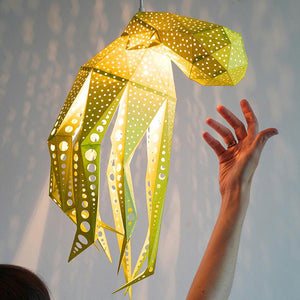 Woman's hands reach out for the yellow Octopus lantern, hanging on a white background.