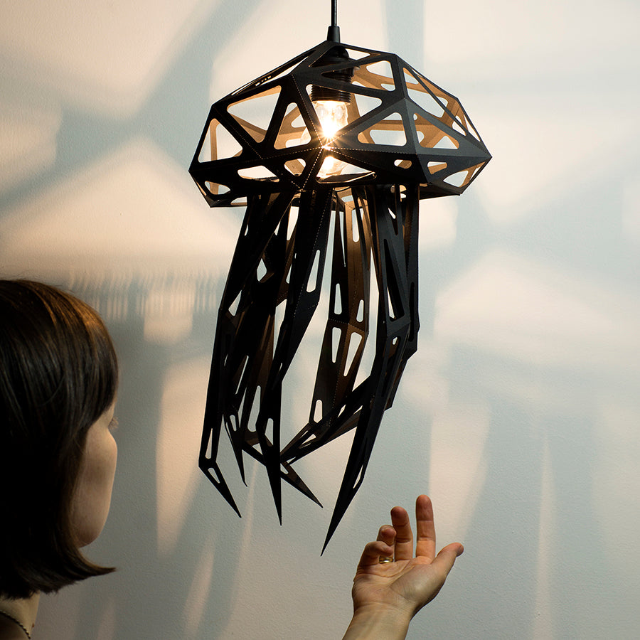 Black pendant lampshade in the form of Jellyfish, white background, woman's hands reaching out for the lampshade.