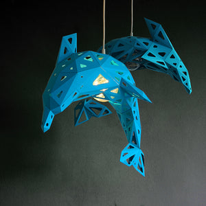 Two blue pendant Dolphin papercraft lampshades hang in a dark room, dark background wall.