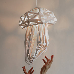 White pendant lampshade in the form of Jellyfish, white background, woman's hands reaching out for the lampshade.