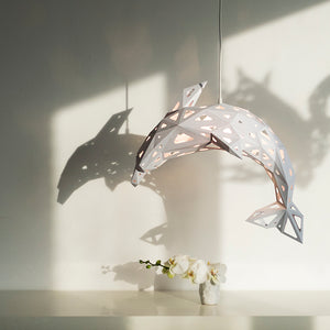 Pendant papercraft lampshade shaped as Dolphin, hanging above  a vase with a flower, shadows on the white wall.