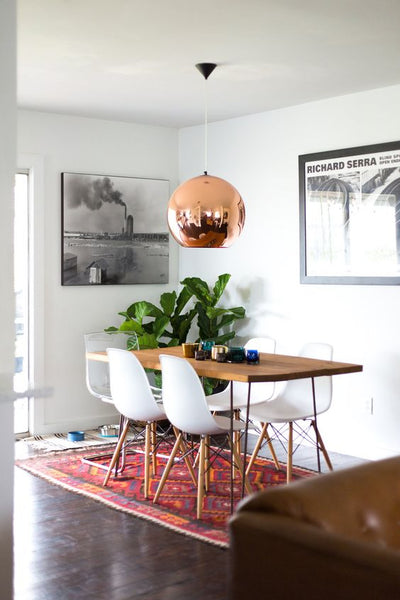 Beautiful, colorful rug with white walls and metal bronze chandelier.