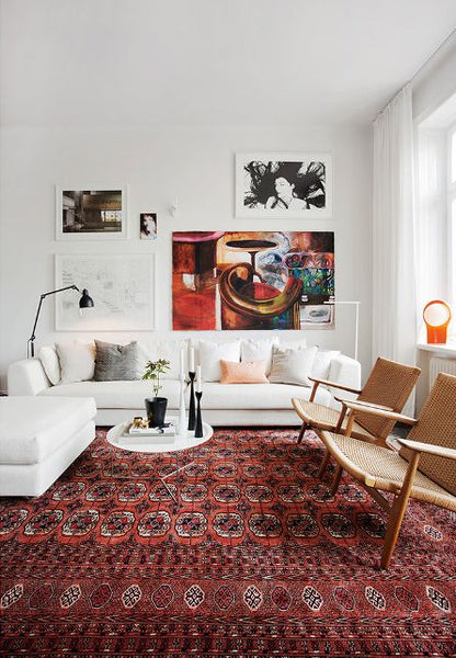 Red oriental rug in a minimalist white room.