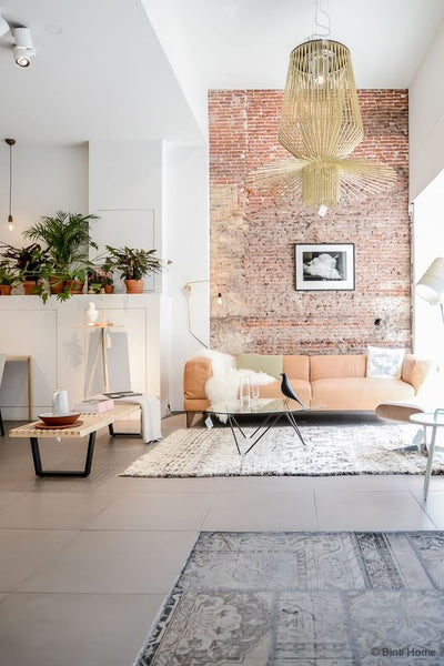 Beautiful oriental rugs and exposed brick against white walls in living room
