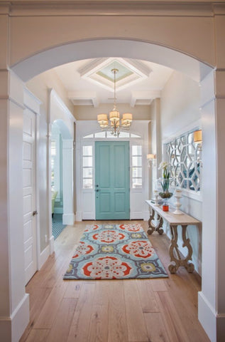 Oriental rug in an entryway with hardwood floors and white walls