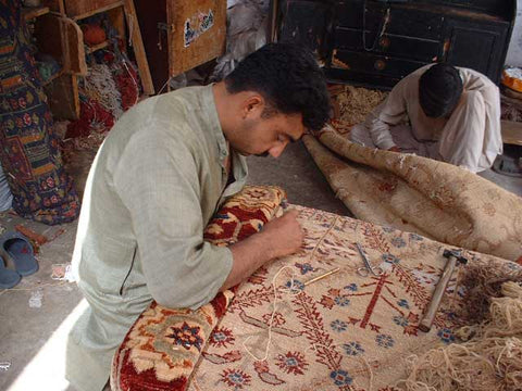 A Pak Persian rug getting hand knotted by an artisan