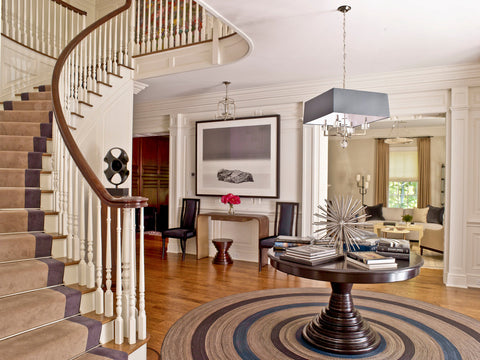 Round area rug in a foyer with a winding staircase in the backroung