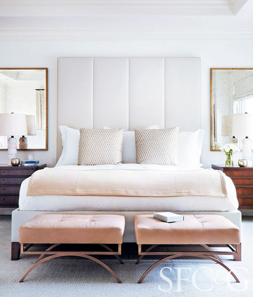 Bedroom with white walls, white headboard, antique brass mirrors, wood bedside tables, light pink ottoman and blanket, patterned pillows, and light carpeted floors: