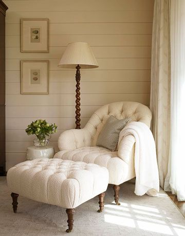 Peaceful reading nook with a tufted chair & ottoman, wood paneled walls, and spiral reading lamp: