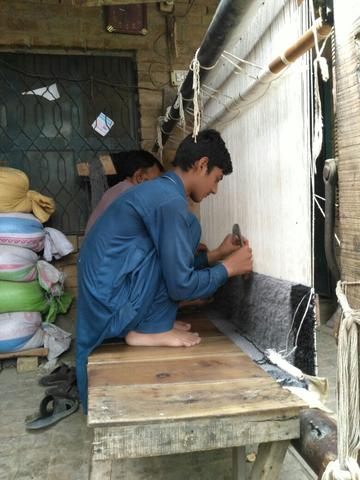 Pakistani man hand knotting a custom made oriental rug