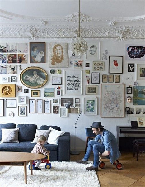 This gallery wall, with lots of smaller pieces in smaller frames, acts as an extension of the texture of the wall. And once again, we've got a lot of white pieces that are blending into the wall and providing a visual break.: