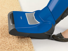 how to clean wool rugs-foot pedal on vacuum being pushed to raise head onto rug fringe.