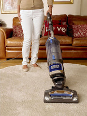 clean wool rugs-clean persian rug-Woman running the shark vacuum cleaner across her shag carpet rug