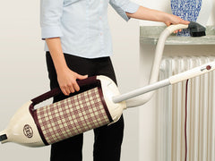 how to clean wool rug Woman vacuuming rug holding a Sebo vacuum